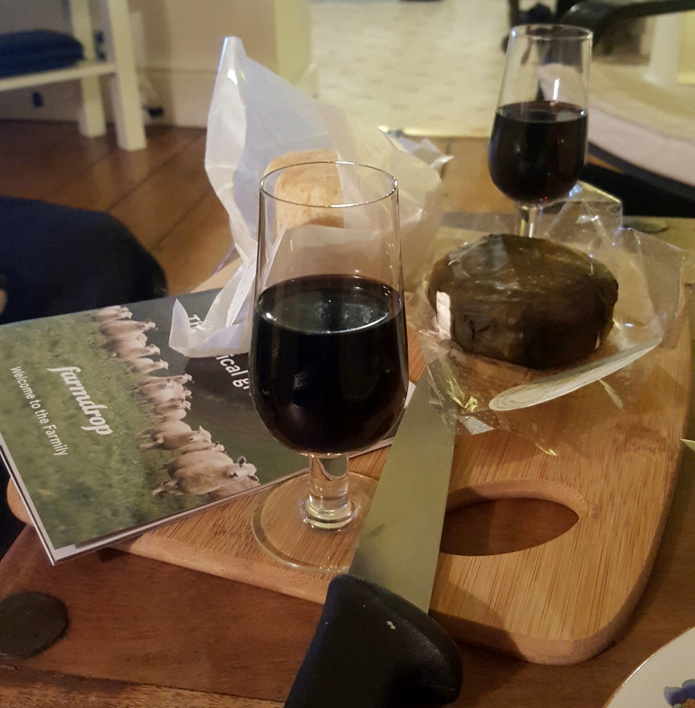 two glasses of port next to two rounds of cheese