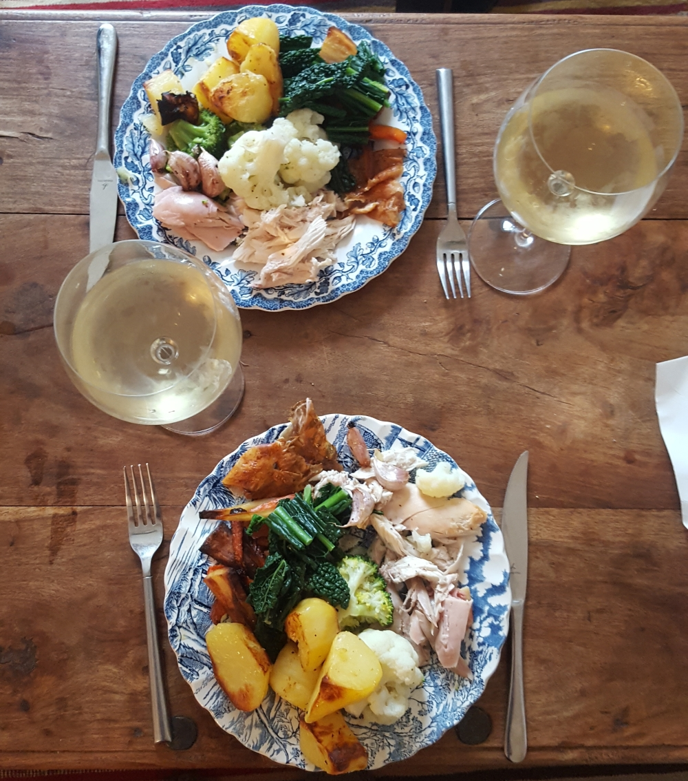 Two plates of roast dinner and two glasses of wine from above