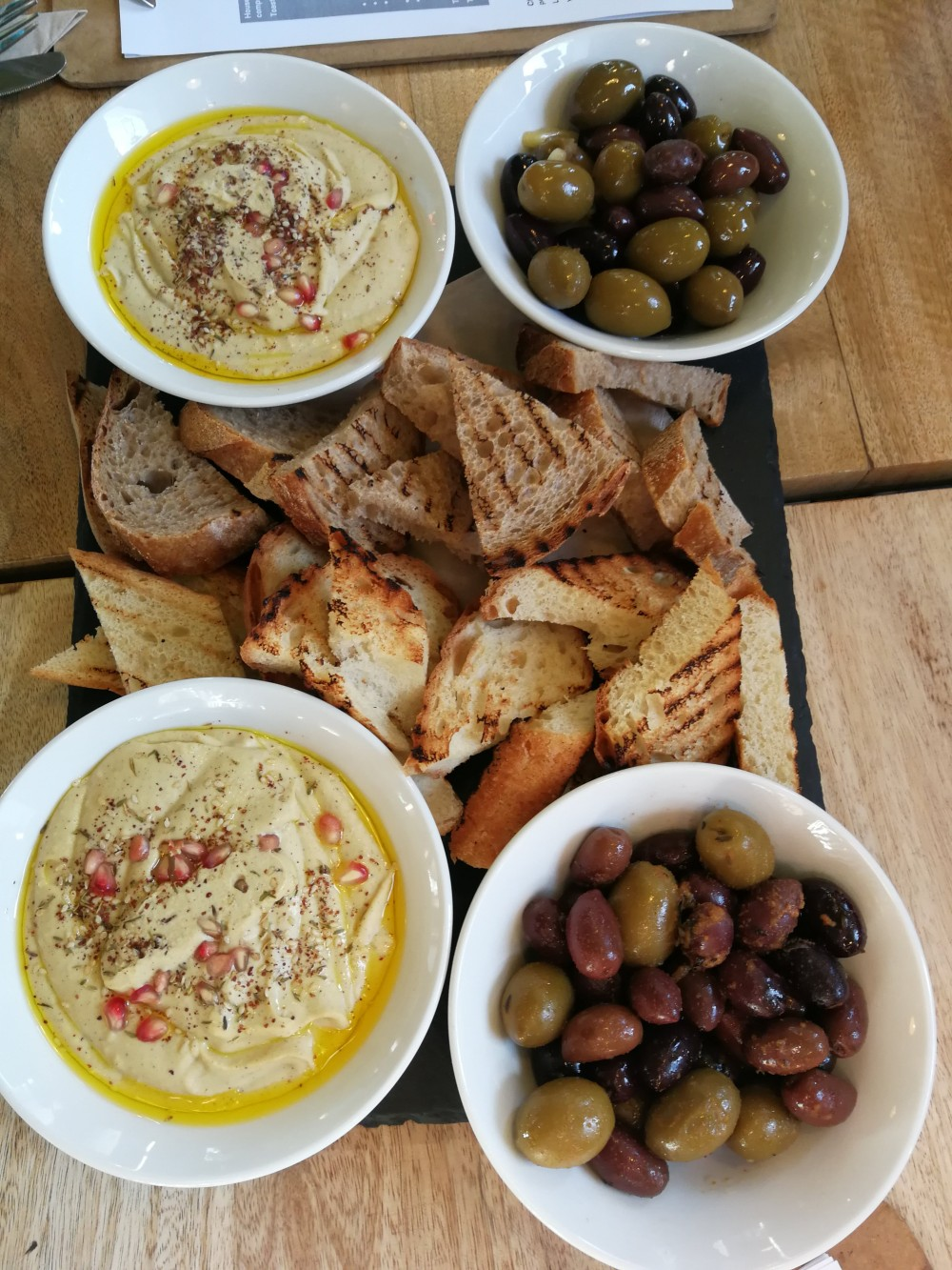 Hummus, bread and olives - photo from above