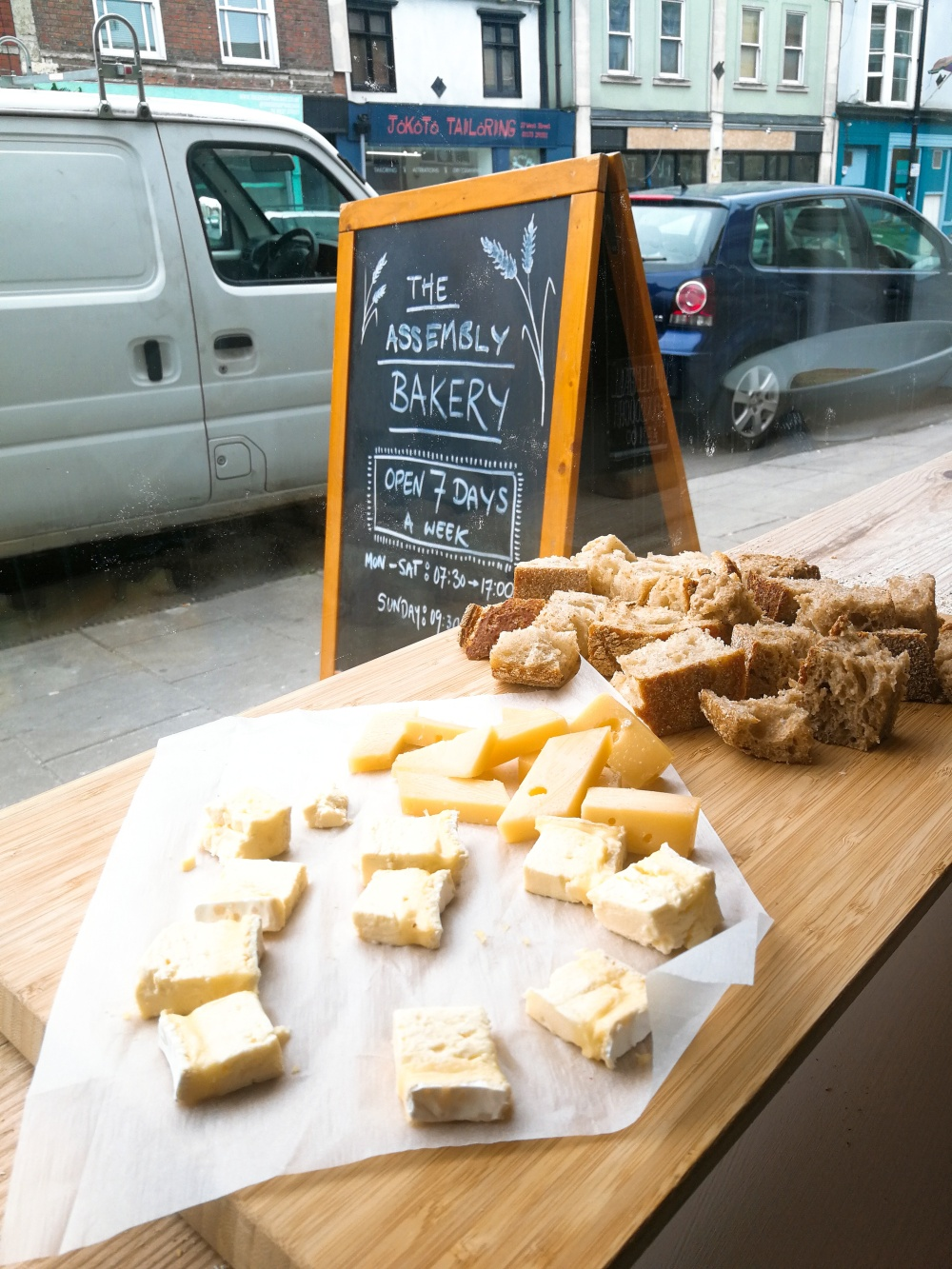 Bites of cheese and chunks of sourdough on a wooden board in a window