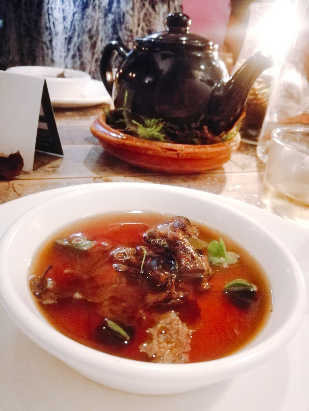 A Forest Consomme with teapot in the background