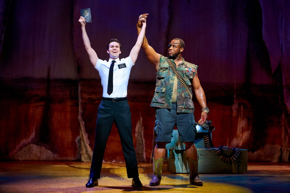 Elder with arms aloft holding the Book of Mormon, holding hands with the General