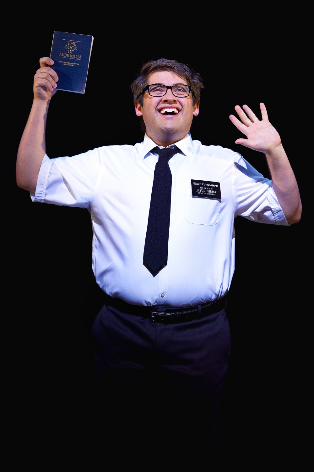 Elder Cunningham waving and holding The Book of Mormon
